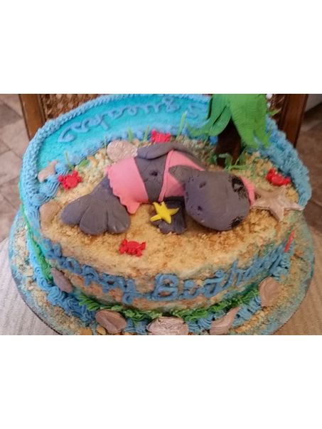 Hand sculpted sunbathing manatee adorns this fun beach themed birthday cake