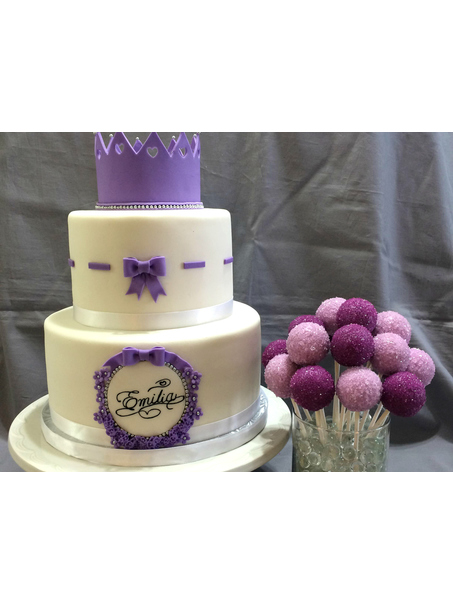 A purple princess themed birthday cake with matching purple cake pops!