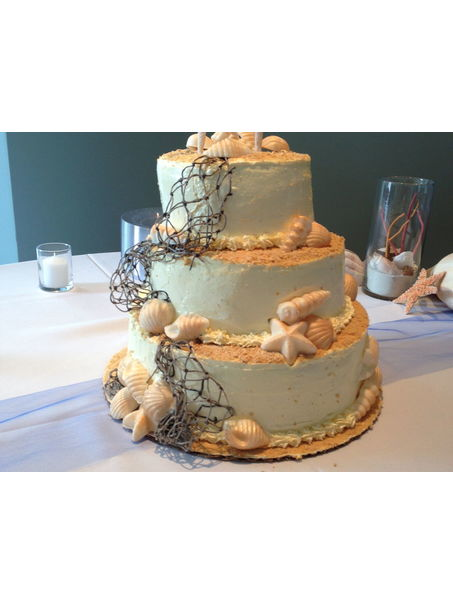 2 - tier cake with ivory frosting and candy shells