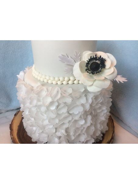 Two tier wafer paper wedding cake with gum paste flowers .
